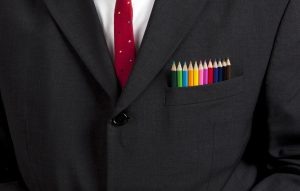 chest of man in business suit with color pencils in his pocket
